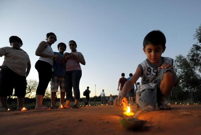 Un niño que formó parte de las celebraciones en San Ignacio Misiones, enciende una de las luminarias.